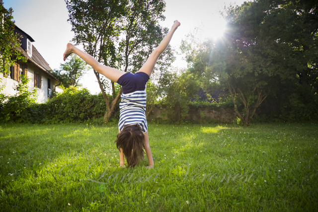 Mädchen macht Handstand/schlägt Rad