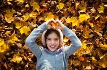 kleines Mädchen mit Mütze, Laub, Herbst